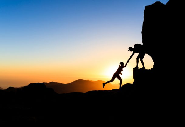 One partner helping another climb up a boulder against a sunset.