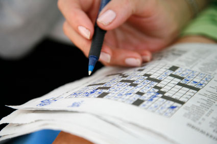 This is a photo of an individual completing a crossword puzzle in pen.