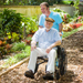 person_pushing_elderly_man_in_sunshine_thumbnail