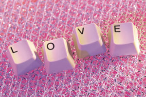 This is a photo of pink computer keys that spell out the word love on some pink lace