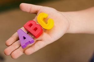 This is a photo of a child holding blocks shaped like letters of the alphabet.