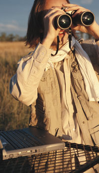 This is a photo of a person in a field holding a pair of binoculars.