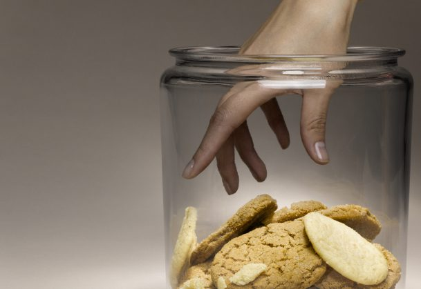 Woman reaching for cookies in cookie jar, close-up of hand