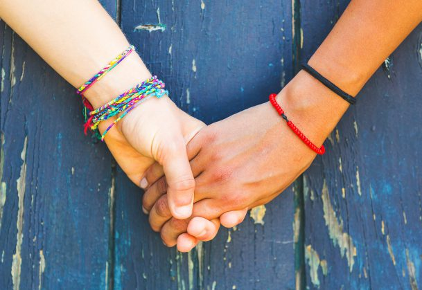 Teens holding hands with a wooden background.
