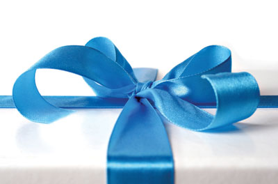 This is a photo of a present with a bow. Read the latest psychological science on giving to others, giving yourself more time, and regifting too!