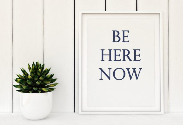 """This is a photo of a framed poster that says """"be here now"""""""