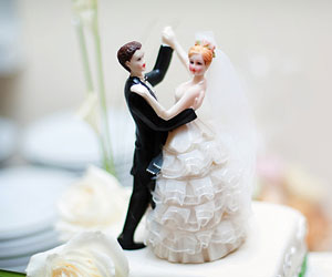 This is a picture of a wedding cake with bride and groom figurines.