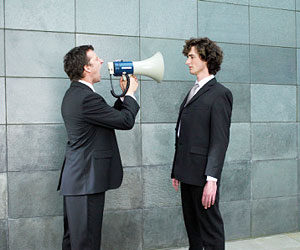 This is a man yelling through a megaphone at another man.