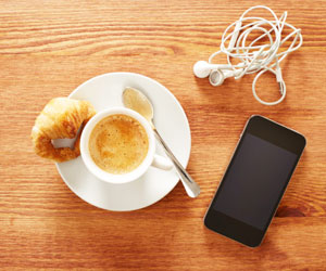 This is a picture of a croissant, an espresso, a smartphone, and headphones.