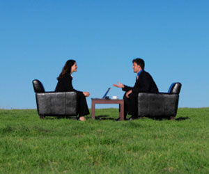 This is a picture of two business people talking in a field.