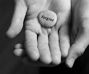 "This is a photo of hands holding a stone with the word ""forgive"" on it."