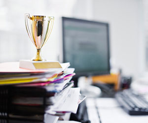This is a photo of a tiny trophy on top of a stack of office papers.