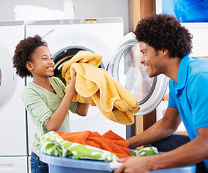 This is a photo of a father and daughter doing laundry.