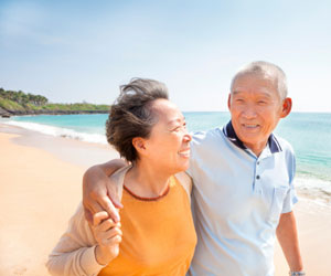 This is a picture of an elderly Asian couple taking a walk on the beach.