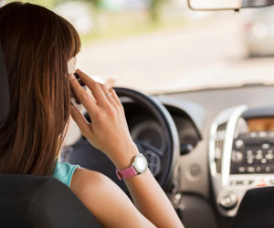 This is a photo of a woman talking on the phone while driving.