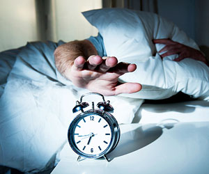 This is a photo of a person reaching to turn off an alarm clock.