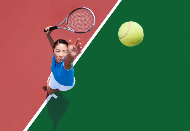 Young Asian woman serving tennis ball.