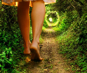 This is a photo of a young woman walking on a path.