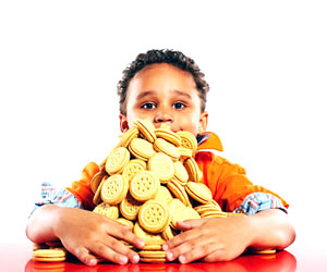 This is a photo of a child with a huge pile of cookies.
