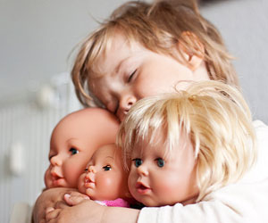 This is a photo of a child holding some dolls.
