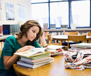This is a photo of a teenage girl reading books.