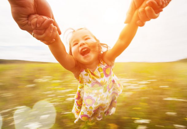 Happy girl spinning around her parent in a field.