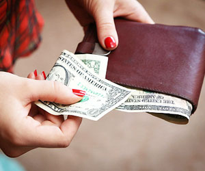 This is a photo of a woman taking cash out of her wallet.