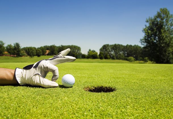 Golfer tipping golf ball into the hole