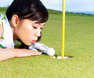 This is a photo of a woman trying to blow her golf ball into the hole.