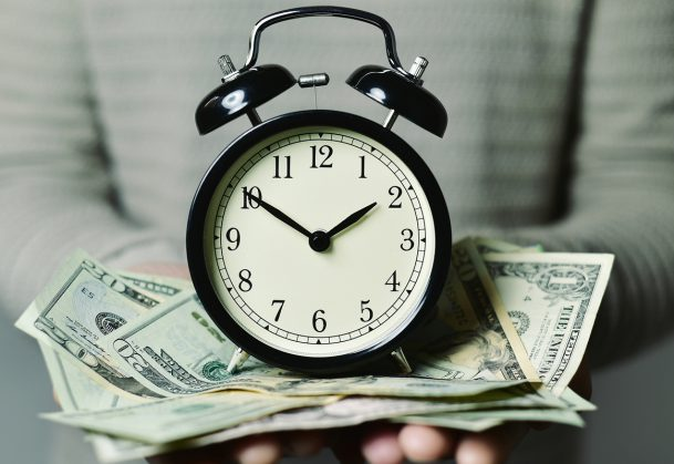 A person holding a clock on top of a pile of paper money