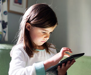 This is a photo of a young girl using a tablet.
