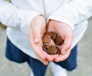 This is a photo of a child holding out pennies.