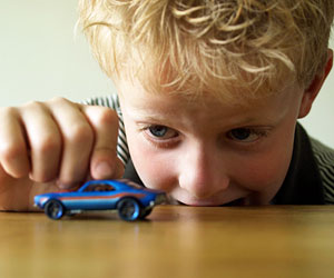 This is an image of a boy playing with a toy car.