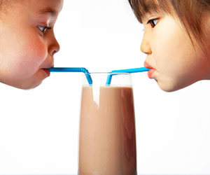 This is a photo of two girls sharing a milkshake.