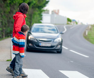 This is a photo of a mother and son at a pedestrian crossing.
