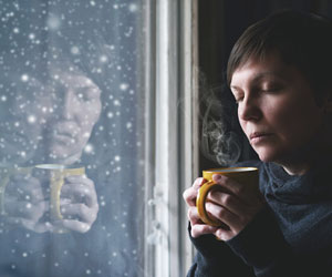 This is a photo of a woman staring out a window.