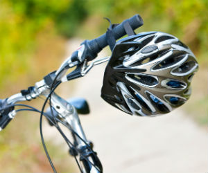 This is a photo of a bicycle helmet hanging from handlebars.