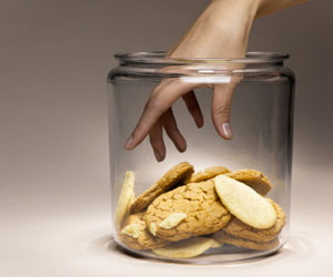 This is a photo of a person's hand reaching into a cookie jar.