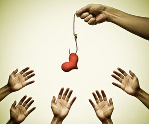 This is a photo of hands reaching toward a heart on a fishing line.