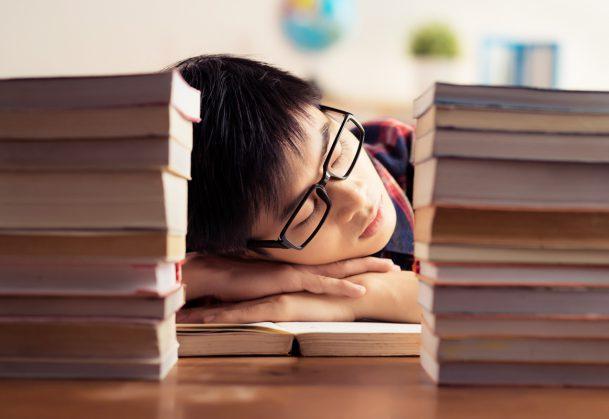 Student sleeping between piles of books