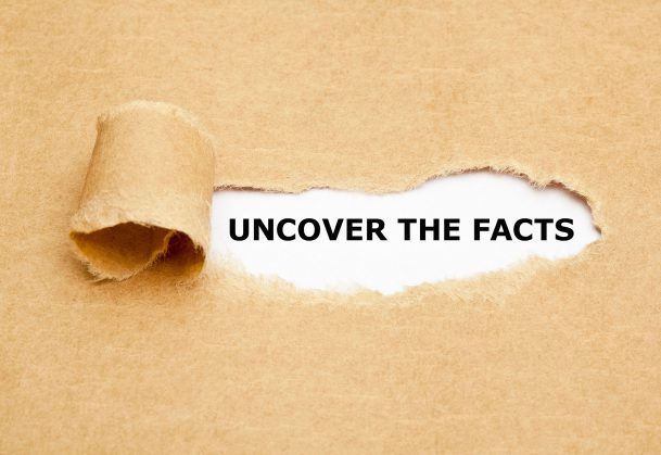 "This is a photo of paper torn back to reveal the phrase ""uncover the facts"""