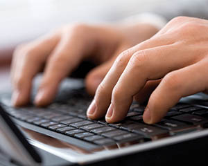 This is a photo of someone typing on a laptop.