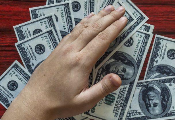 Hands grabbing money from a desk