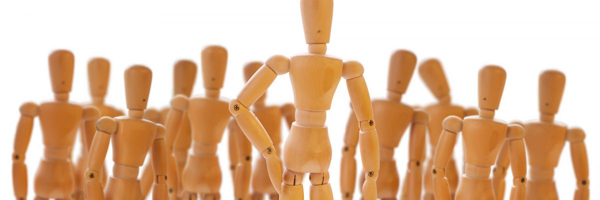Character standing in front of a defocused crowd. Wooden dummies isolated on white.