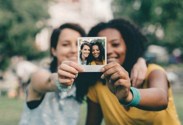 Friends holding a Polaroid photo they took of themselves