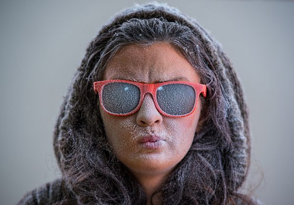 This is a photo of a woman wearing hood and sunglasses with frost on her face.