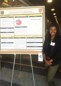 This is a photo of Brittney Green standing next to her poster at a research conference.