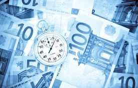 stopwatch on pile of euro banknotes