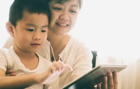 Mother and son using electronic tablet together.