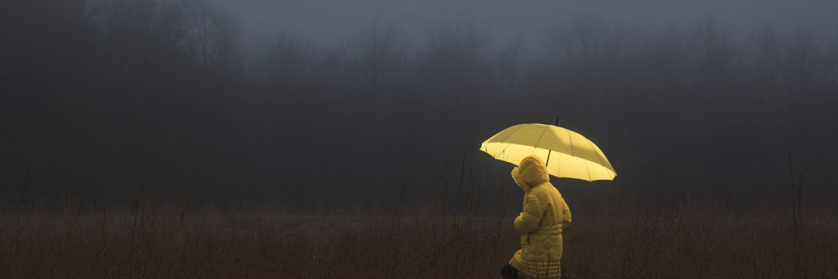 This is a photo of a person with an umbrella crossing a dark field
